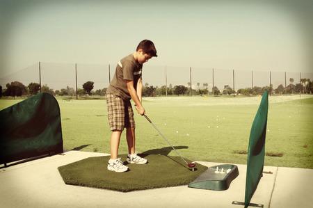 teen golf: Chico joven en el campo de prácticas de golf con un look retro. Foto de archivo