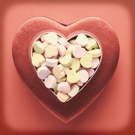 high angle shot: A high angle shot of candy valentines on top of another heart shaped box. Square format with a vintage, faded look and intentional vignette.