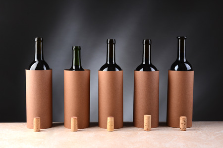 Five different wine bottles set up for a blind wine tasting. The bottles have the corks removed and setting if front of the disguised bottles. Horizontal format. Imagens