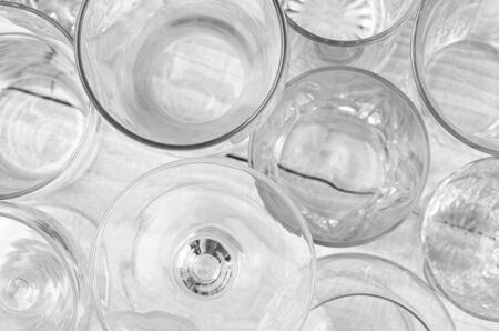 high angle shot: High angle shot of assorted glassware forming an abstract pattern. Horizontal format on a white wood table, with shallow depth of field. Stock Photo