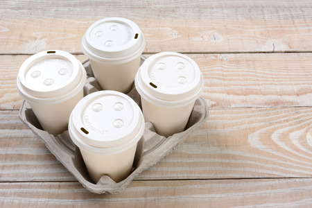 High angle shot of a cardboard take out tray with four coffee cups with lids.
