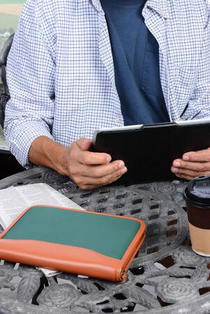 cafe internet: Primer plano de un hombre usando su Tablet PC una de la mesa de un caf� internet al aire libre. Un peri�dico, la taza de caf� y el cuaderno sobre la mesa de hierro fundido.