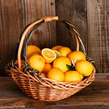 canastas con frutas: Primer plano de una cesta llena de limones delante de una pared de madera rústica y mesa. Formato cuadrado con una fuerte luz de la ventana lateral.