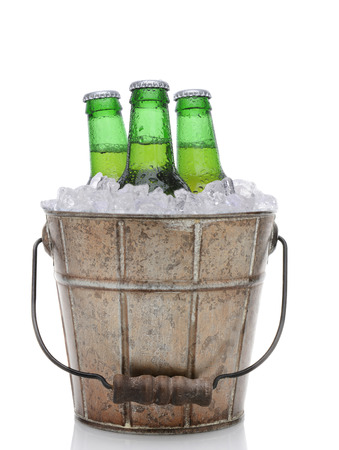 Closeup of an old fashioned beer bucket with three green bottles of cold beer. Isolated on white with reflection. photo