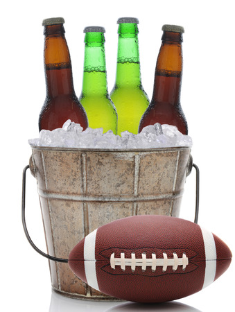 Closeup of an old fashioned beer bucket with three green bottles of cold beer and an American Football. Isolated on white with reflection. photo