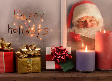 homey: Happy Holidays written in the frost of a window with Santa Claus looking in the other pane holding a wrapped present. Inside the window ledge has presents and lighted candles. Stock Photo