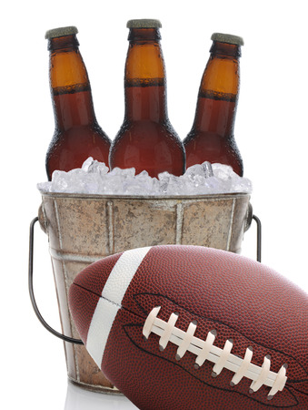 An old metal bucket with three brown beer bottles covered in condensation on a white background. An American football at an angle sits in front of the pail. photo