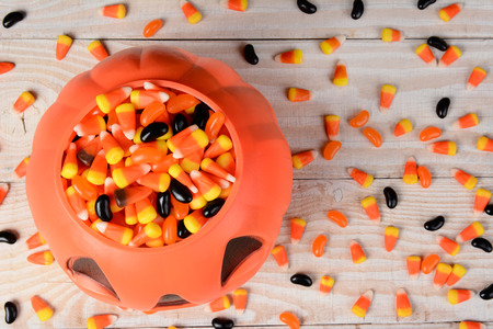 high angle shot: High angle shot of a plastic halloween pumpkin filled with candy on a white rustic wood table. Horizontal format with candy corn and jelly beans scattered on the surface.