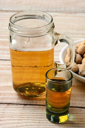 jarra de cerveza: Primer plano de un trago de whisky, una jarra de cerveza y un plato de cacahuetes. Formato vertical sobre una mesa de madera rústica.