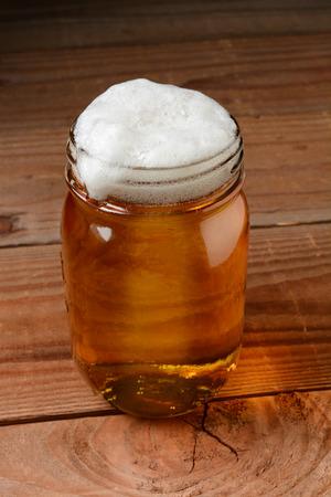 jarra de cerveza: Vaso de cerveza en un ambiente de bar país sirve en un frasco de conservas. Formato vertical sobre un fondo de madera rústica.