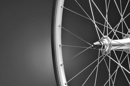 Closeup of a bicycle wheel on a light to dark black and white background. Only half of the wheel is shown. Horizontal format with copy space. Stock Photo