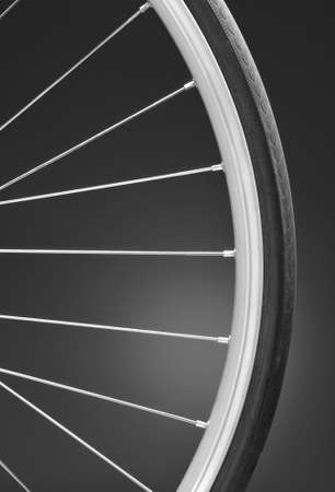 Closeup of a bicycle wheel on a light to dark black and white background. Only part of the wheel is shown. Vertical format with copy space. photo