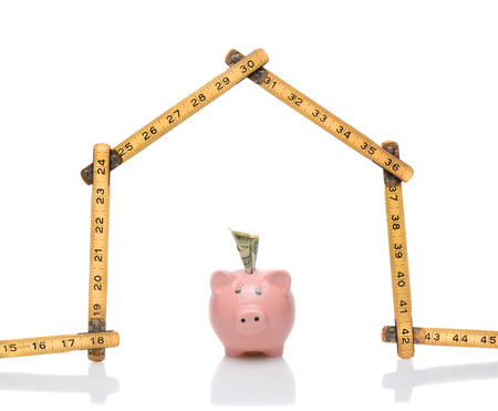 escrow: A carpenters ruler in the shape of a house with a piggy bank under the roof. Horizontal format on white with reflections. Great for housing cost and budget concepts.