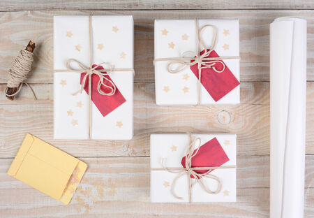 adorn: High angle shot of Christmas presents wrapped in white paper and tied with white string. Red gift tags and stars adorn the packages on a white wood table. Stock Photo