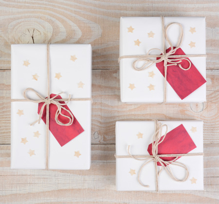 adorn: High angle image of Christmas presents wrapped in white paper and tied with white string. Red gift tags and stars adorn the packages on a white wood table. Square format.