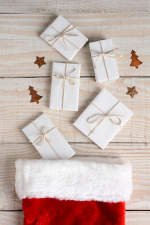 High angle image of a Christmas Stocking with five plain white paper wrrapped gifts tied with string on a whitewashed wood table. Vertical Format. photo