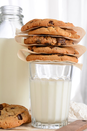 chocolate chip cookies: Closeup of a stack of fresh baked cookies on top of a glass of milk. Vertical format with a bottle of milk and flour in the background. Chocolate Chip, Oatmeal Raisin, White Chocolate cookies.
