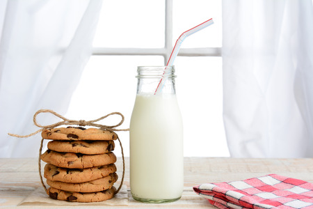Horizontal shot of an after school snack of chocolate chip cookies and an old fashioned bottle of milk. The cookies are tied with twine and with a napkin on a rustic wood kitchen table.