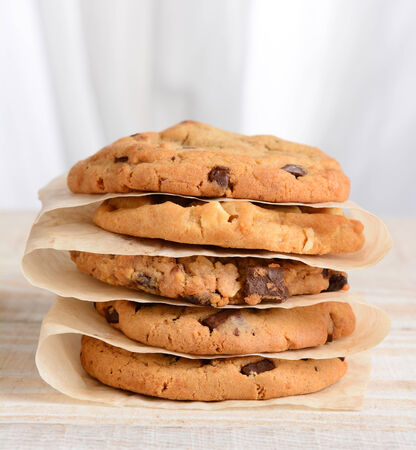 Closeup of a stack of fresh baked cookies Chocolate Chip, Oatmeal Raisin, White Chocolate Chip cookies on parchment paper. Square format on a rustic white kitchen table. photo