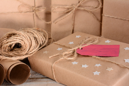 adorn: Closeup of a group of Christmas packages wrapped with plain brown paper and twine. Horizontal format on a wood table. A red gift tag and paper stars adorn one parcel. Stock Photo
