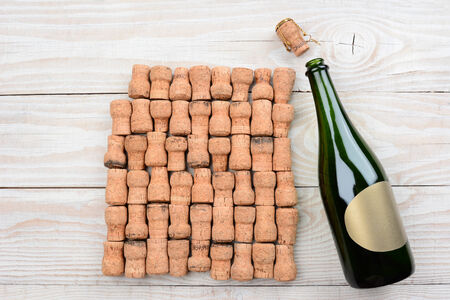 high angle shot: HIgh angle shot of a empty champagne bottle with blank label and corks. Closeup on a rustic white wood table. Horizontal format with copy space.