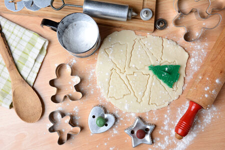 cookie cutters: Baking holiday cookies still life shot form a high angle. Horizontal format with cookie dough, cutters, sifter, flour, rolling pin, cookie press, spoon, towel on butcher block surface.