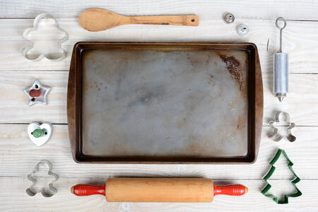 white sheet: Overhead shot of a group of items for baking Christmas Cookies surrounding an empty cookie sheet. Horizontal format on a  rustic wood kitchen table.