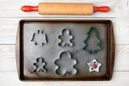 Overhead image of an old fashioned rolling pin and a cookie sheet with different holiday cookie cutters. Horizontal format on a rustic white wood kitchen table. photo