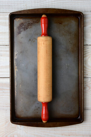 cookie sheet: High angle closeup of an old wooden rolling pin with red handles on a well used cookie sheet. The pan is on a rustic white kitchen table. Vertical format.