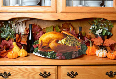 the hutch: Thanksgiving turkey on a sideboard. The still life has fall leaves, pumpkins and decorative gourds wine bottles. The turkey is stuffed with garnish surrounding it on the platter. Stock Photo