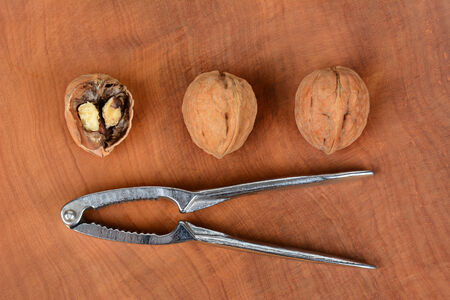 high angle shot: High angle shot of three walnuts and a nutcracker on a wood surface, one nut is cracked in half. Horizontal format.