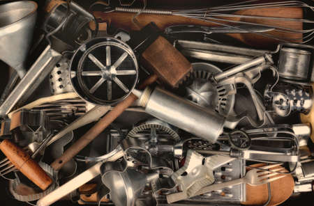 old items: Closeup of a group of old metal and wood kitchen utensils. Items include: sifter, funnel, cookie cutters, forks, mallet, corkscrew, mixer, beater, whisk, press, spoon, grater and more.