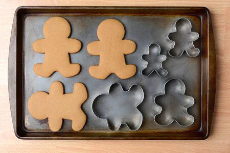 cookie sheet: High angle shot of an old baking sheet with holiday gingerbread man cookies and cookie cutters. Horizontal format on wood kitchen table.