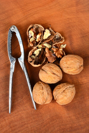 high angle shot: High angle shot of some walnuts and a nutcracker on a wood surface, one nut is cracked in half. Vertical format.