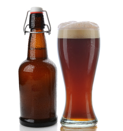 brown bottle: Closeup of a glass of dark beer with a frothy head next to a swing top brown beer bottle. Straight on shot on a white background with reflection. Both items are cover with water drops.