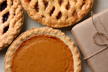High angle closeup of three fresh baked holiday pies and a plain paper wrapped package. The traditional anerican desserts - Pumpkin, Cherry and Apple pie are Thanksgiving staples. Horizontal format.
