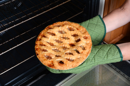 Closeup of a woman taking a fresh baked apple pie from the oven. Apple Pie is a traditional American dessert for Holiday feasts. Horizontal showing the womans hands in oven mitts only.