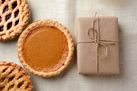 High angle shot of three holiday pies and a wrapped parcel on a burlap tablecloth. The cherry and apple pies run out of the frame with a whole pumpkin pie and package dominate the frame. photo