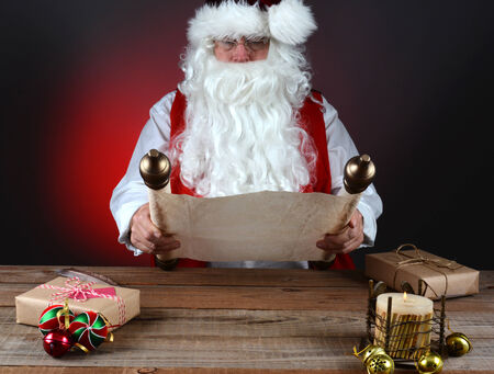 naughty or nice: Santa Claus holding his Naughty and Nice list on a scroll of parchment paper. Stock Photo