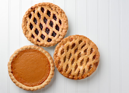 High angle shot of three pies, apple, pumpkin, and cherry. Horizontal format on a white beadboard surface. Thes pies are favorites for the  American Holidays, Thanksgiving and Christmas.
