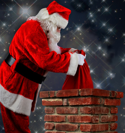 st nick: Closeup of Santa Claus placing his bag of toys into a chimney. Vertical format over a starry nightime backgorund. Stock Photo