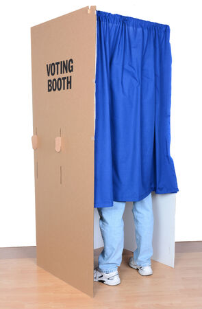 anonymity: A man standing behind the curtain of a voting booth, The cardboard booth has a blue curtain to protect anonymity. Vertical format with a white background.