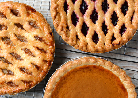 Three pies on cooling racks. High angle closeup shot of fresh baked apple, cherry and pumpkin pies on wire racks on a rustic wood kitchen table. Horizontal format. Stockfoto