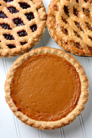 High angle closeup of three fresh baked holiday pies. The traditional American desserts - Pumpkin, Cherry and Apple pie are Thanksgiving staples. Vertical format. photo