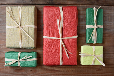 high angle shot: High angle shot of a group of presents wrapped with colorful tissue paper. The gifts are tied with raffia and are laying on a rustic wood table. Horizontal format.