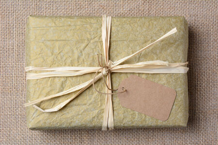 git: Closeup of a gold tissue paper wrapped present on a burlap surface. The gift is tied with raffia and a blank git tag. High angle shot in horizontal format.