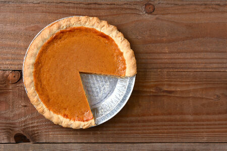 pumpkin pie: A pumpkin pie with a slice cut out. Horizontal format on a rustic wood table.