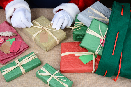 st nick: Closeup of Santa Claus wrapping presents. Only Santas hands are visible as he puts the finishing touches on a variety of gift boxes next to his bag on Christmas Eve. Horizontal Format. Stock Photo