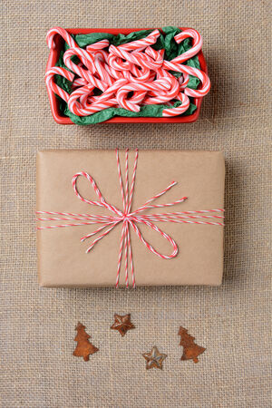 high angle shot: High angle shot of a bowl full of mini candy canes, a plain paper wrapped Christmas present and tree and star antique decorations on a burlap surface. Vertical Format.