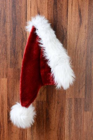 Closeup of a Santa Claus hat hanging from a nail on a rustic wooden wall.  Vertical Format. Banque d'images